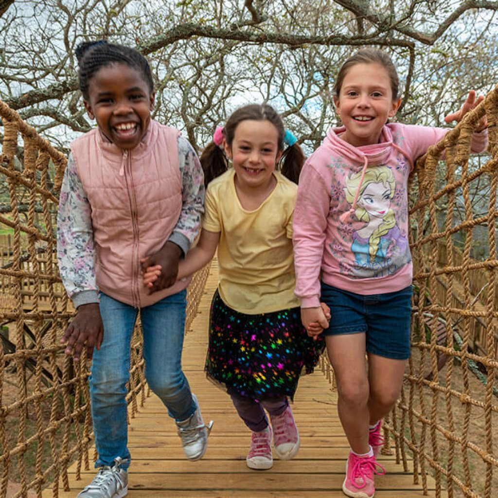 Three kids laughing holding hands walking over a bridge